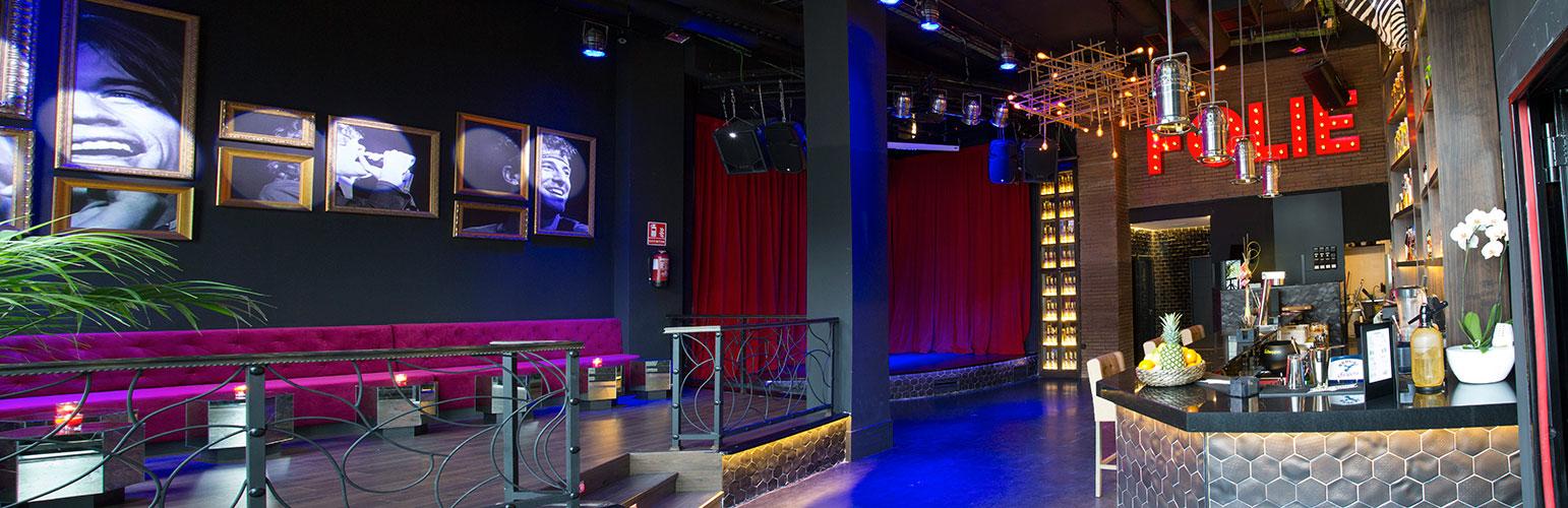 Panorámica sala principal Folie: sillones, cuadros, escenario y barra.